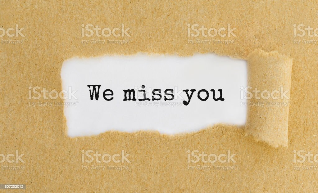 Text We Miss You Appearing Behind Ripped Brown Paper Stock Photo