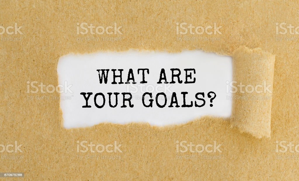 Text What Are Your Goals appearing behind ripped brown paper. stock photo