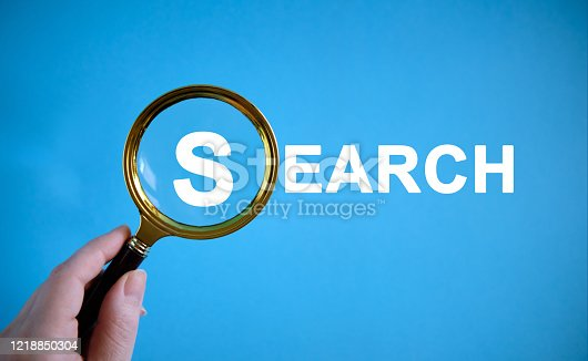 istock SEARCH - text with a magnifying glass on a blue background 1218850304