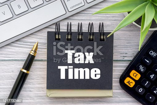 1136634036 istock photo TAX TIME text with decorative flower, calculator, fountain pen, keyboard and notepad on wooden background 1217732467