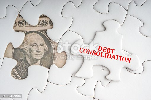 DEBT CONSOLIDATION text with Dollar banknotes on white jigsaw puzzle. Business and copy space concept