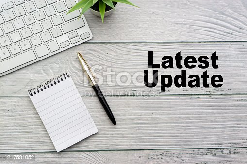 istock LATEST UPDATE text with notepad, keyboard, decorative vase and fountain pen on wooden background. 1217531052