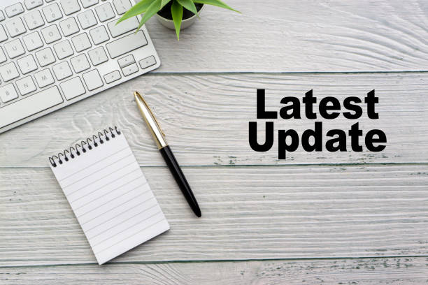 LATEST UPDATE text with notepad, keyboard, decorative vase and fountain pen on wooden background. LATEST UPDATE text with notepad, keyboard, decorative vase and fountain pen on wooden background. Business and copy space concept update communication stock pictures, royalty-free photos & images