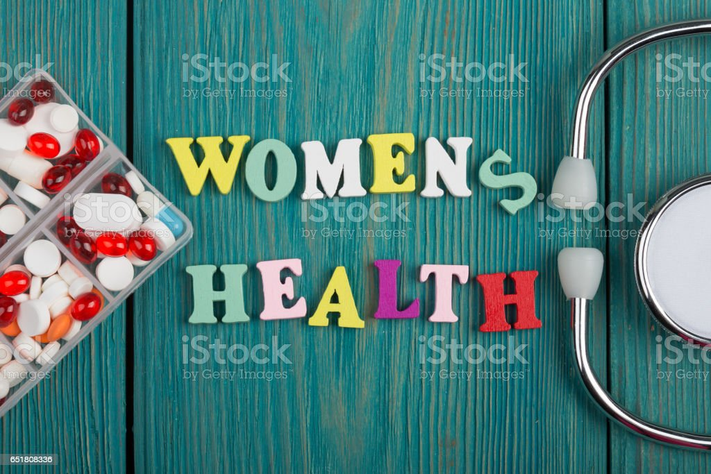 Text 'Women's health' of colored wooden letters, stethoscope and pills stock photo