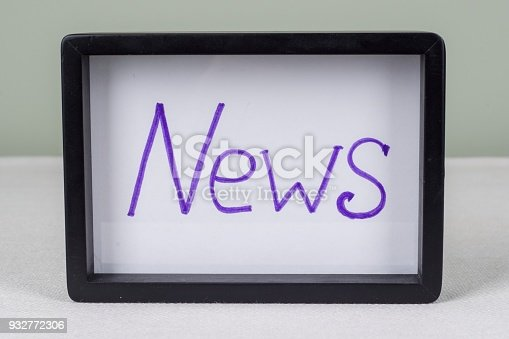 546439334 istock photo Text word NEWS, in black frame, on white table. 932772306