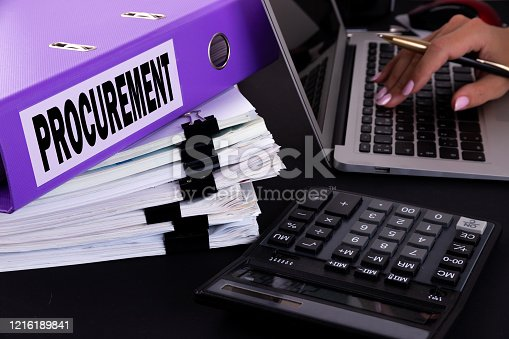 628418378 istock photo Text, word Procurement is written on a folder lying on documents on an office desk with a laptop and a calculator. Business concept. 1216189841