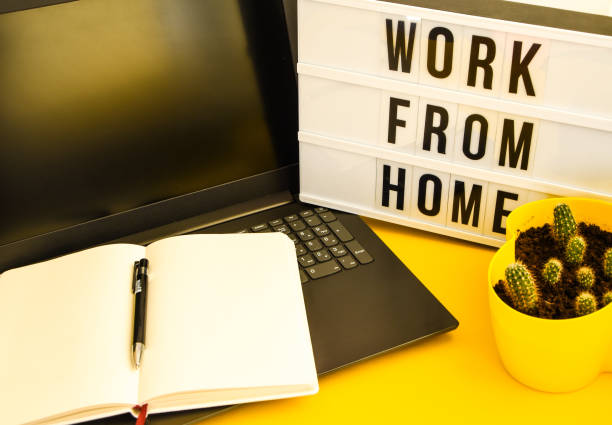 Text WORK FROM HOME with notebook, laptop and pen, cactus, work from home place, freelance environment on yellow background copy space stock photo