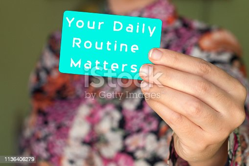 text writing Your Daily Routine Matters on card holding by businesswoman