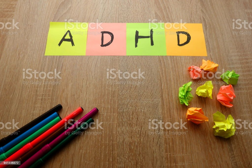 ADHD text written on colorful sheets of paper stock photo