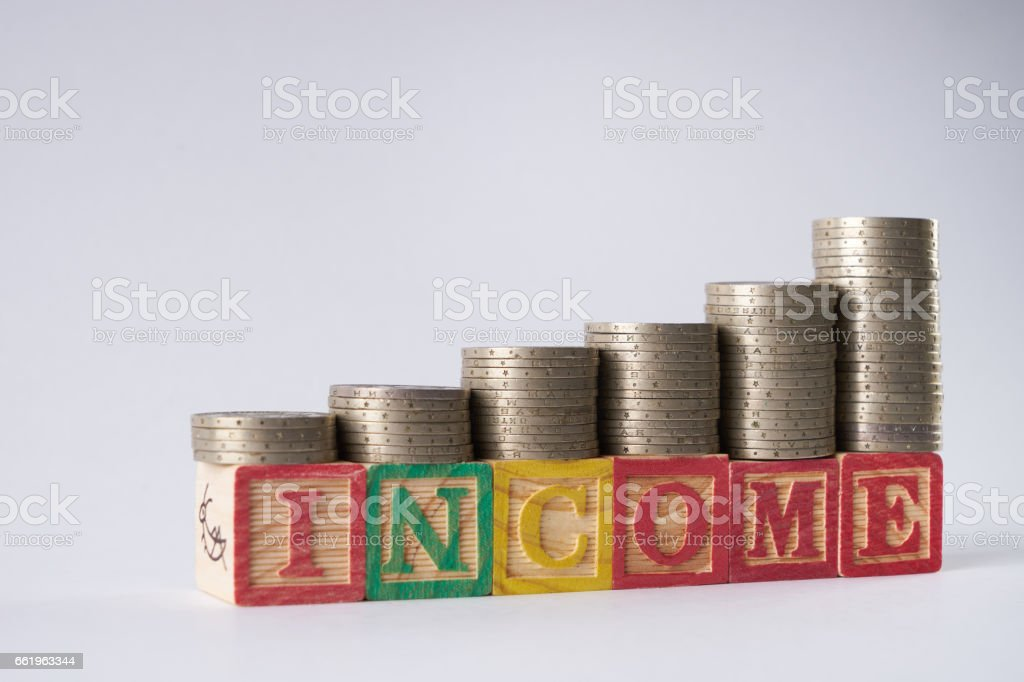 INCOME text written on wooden blocks with stacked silver coins royalty-free stock photo