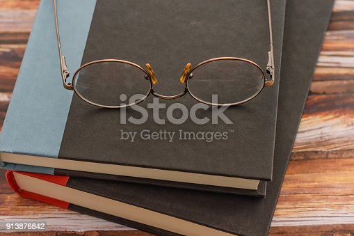 1034955096 istock photo Textbooks and glasses on wood background 913876842