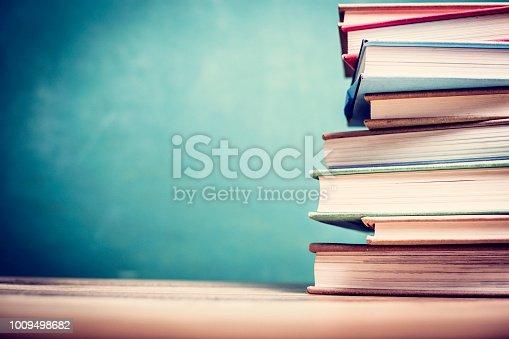 istock Textbooks on wooden school desk with chalkboard. 1009498682