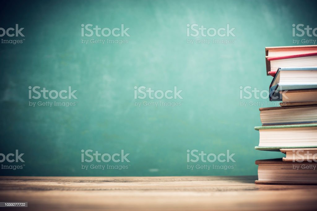 Textbooks on wooden school desk with chalkboard. foto stock royalty-free