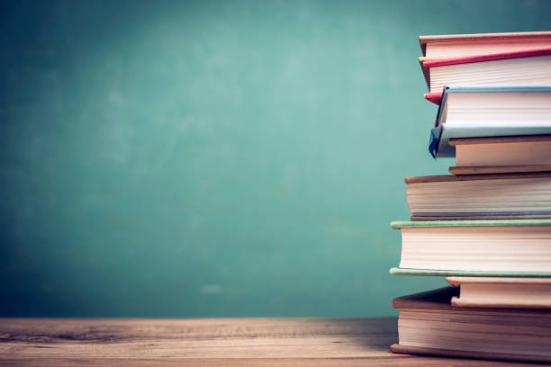 Textbooks on wooden school desk with chalkboard. stock photo