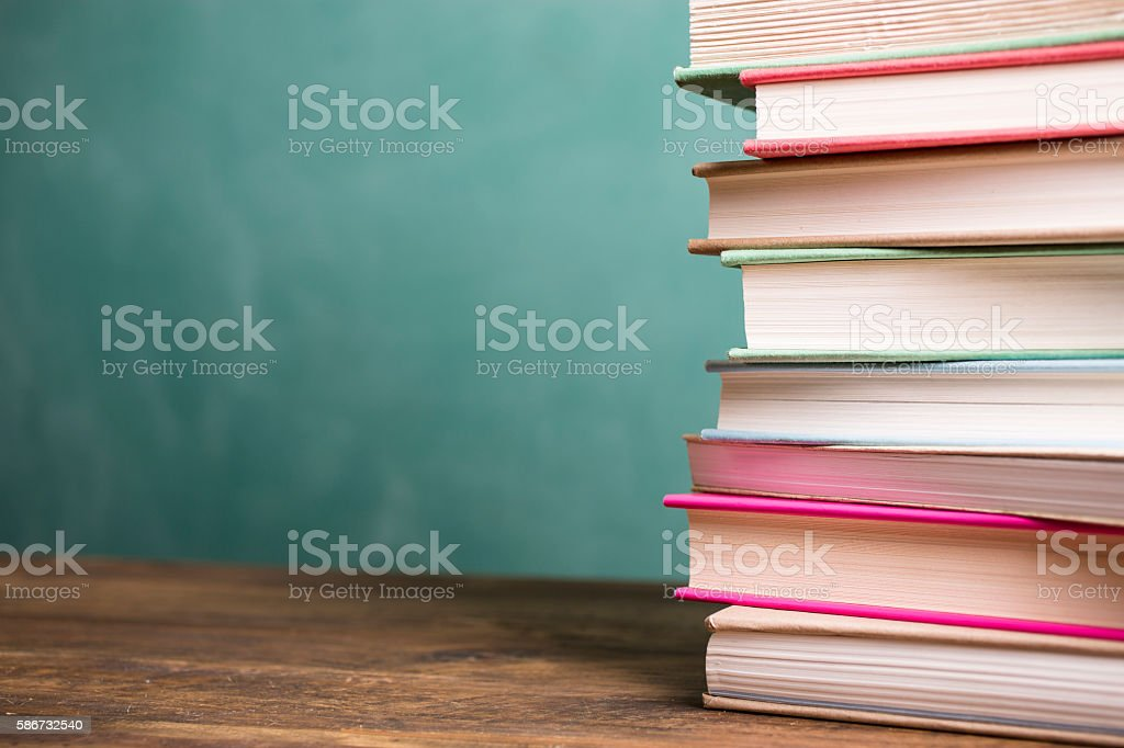Textbooks Stacked On School Desk With Chalkboard Background ...
