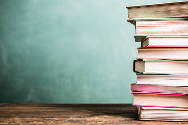 Textbooks stacked on school desk with chalkboard background. stock photo