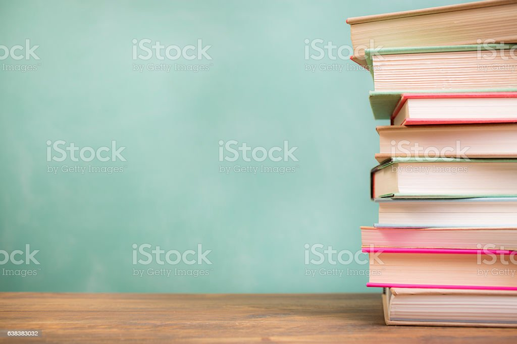 Textbooks stacked on school desk with chalkboard background.​​​ foto