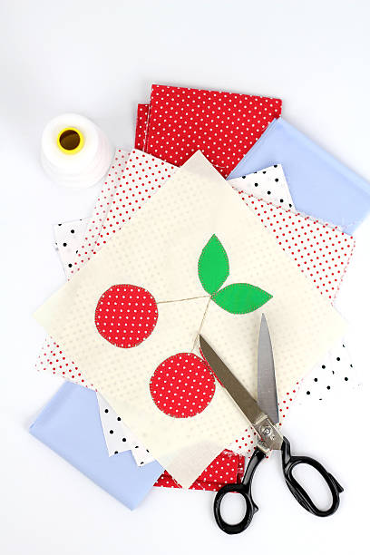 Textile applique with cherries, polka dot fabrics, scissors and thread stock photo