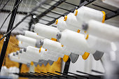 Textile factory. Equipment with spools of white yarn