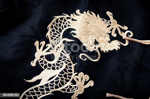 532522827 istock photo Textile gold chinese dragon pattern sewn on black silk 584888260
