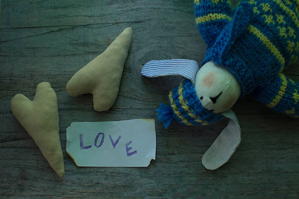 textile rabbit. in knitted sweater, hat and jeans, and two hearts - damen hosen angels stock-fotos und bilder