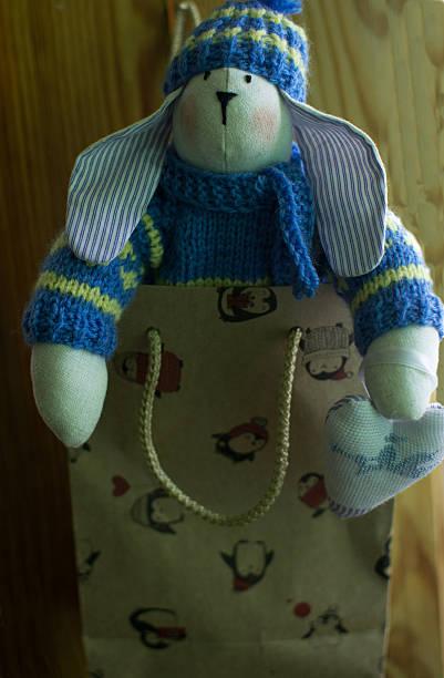 textile rabbit. in knitted sweater, hat, jeans, in gift bag - damen hosen angels stock-fotos und bilder