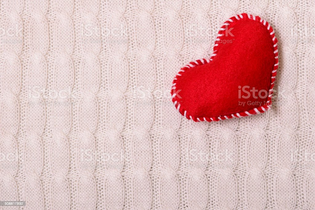 Textile red heart on a knitted texture stock photo