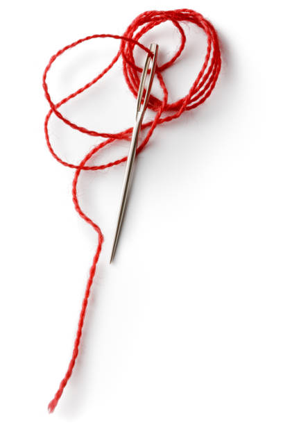 Textile: Red Thread and Needle Isolated on White Background Textile: Red Thread and Needle Isolated on White Background sewing needle stock pictures, royalty-free photos & images