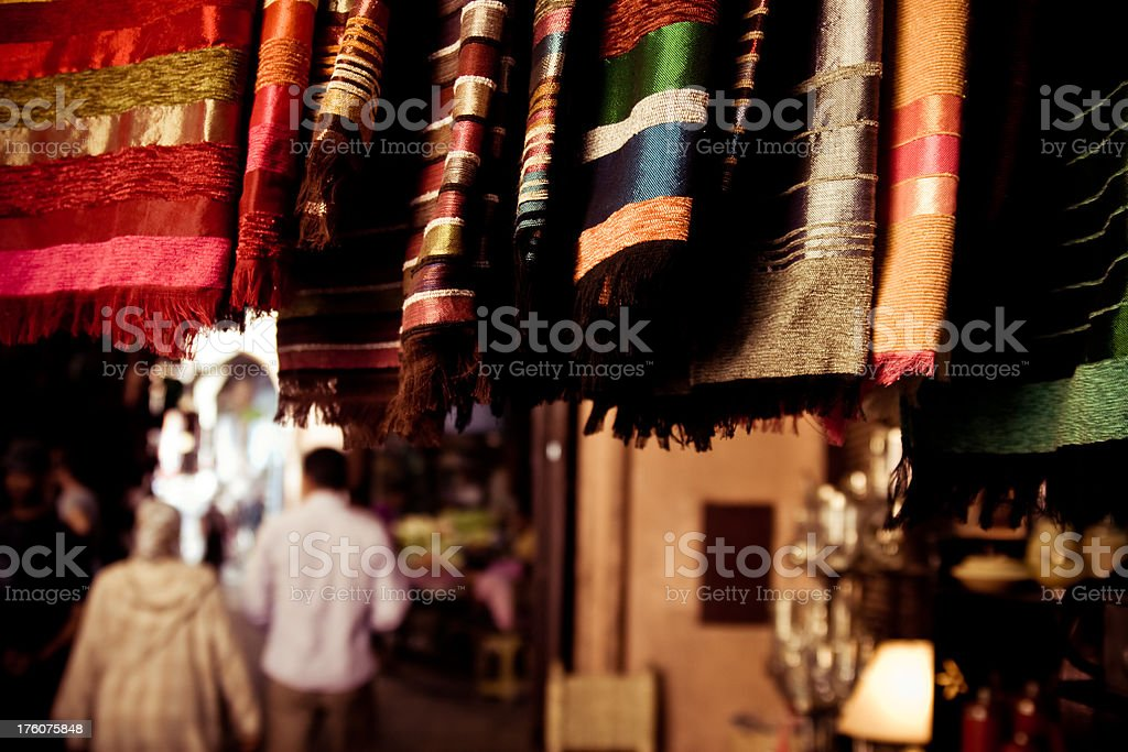 Textiles on the crowded market square in Marrakech royalty-free stock photo