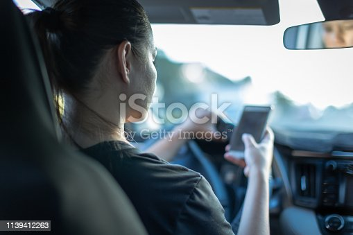 istock Texting and driving. Woman using phone behind the wheel. 1139412263