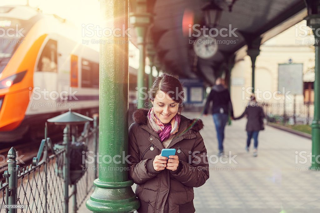 Texting at the train station Woman at the train station text messaging Adult Stock Photo