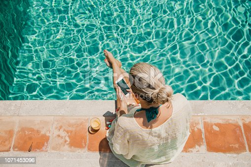 Unrecognisable mature woman sitting on the side the pool with her feet in the water.