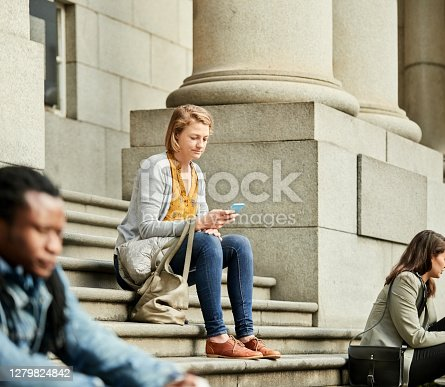 Shot of a young woman sitting on city stairs using mobile phone