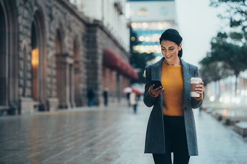 Modern young woman walking on the city street texting and holding cup of coffee