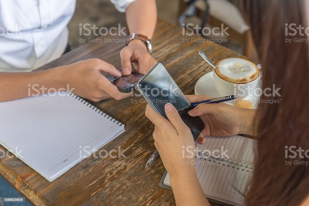 Texting message on smartphone make them lose concentration on conversation stock photo