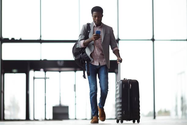 texting on the move - aeroporto foto e immagini stock