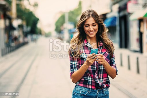 A young woman texting on the phone outdoors.