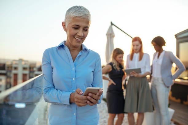 texting on the phone - senior business woman tablet imagens e fotografias de stock