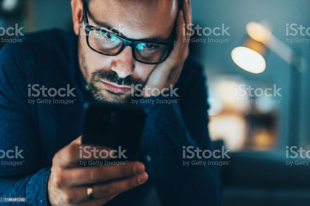 Texting Young man addicted to social media texting in the dusk at home 30-39 Years Stock Photo