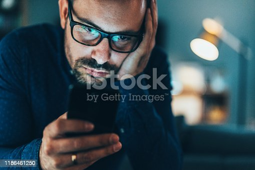 Young man addicted to social media texting in the dusk at home