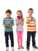 Group of children texting on the phone and using a tablet. They are having fun.