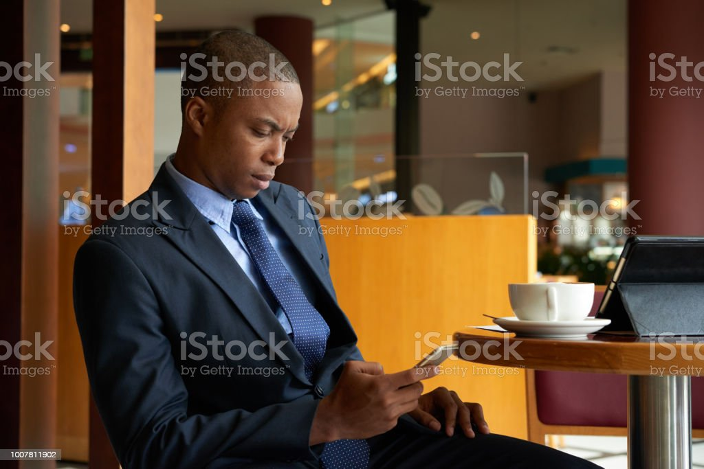 Texting serious entrepreneur Serious frowning businessman sitting at cafe table and checking messages in his smartphone Frowning Stock Photo