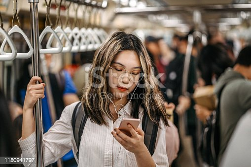Young female student standing in subway train and text messaging on mobile phone