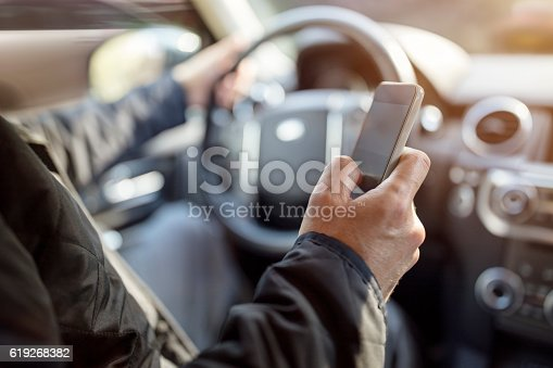 Using a phone in a car texting while driving concept for danger of text message and being distracted