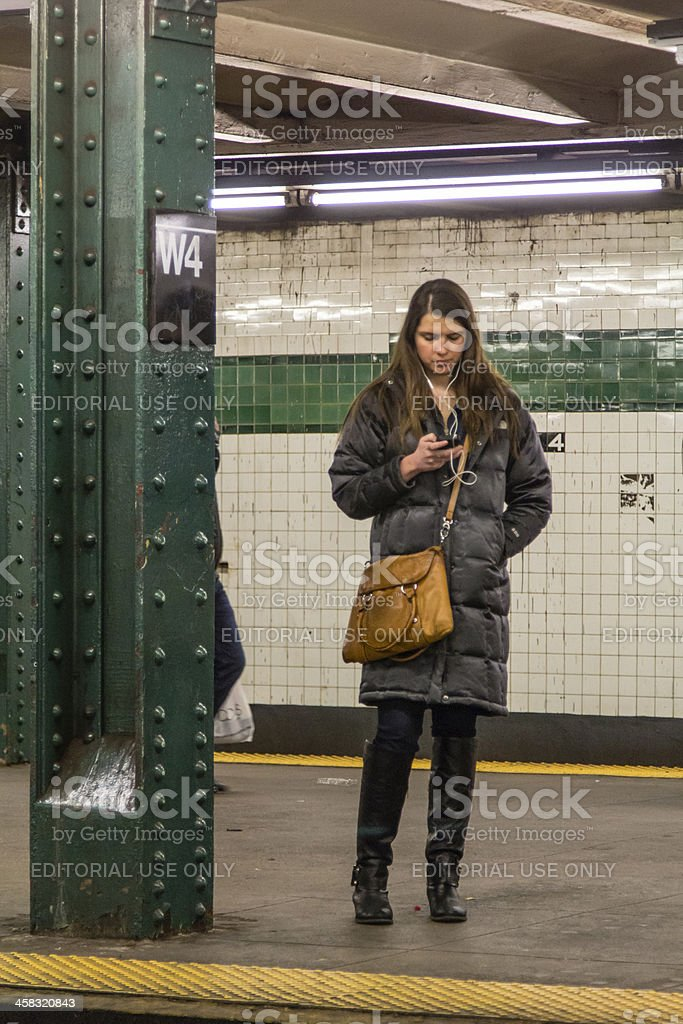 Texting While Waiting For The Subway Train New York City royalty-free stock photo