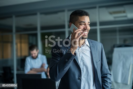 Handsome african american businessman texting on the phone.