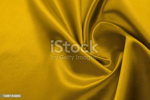 istock Texture, background, pattern. A yellow satin is a silk fabric. 1068184694
