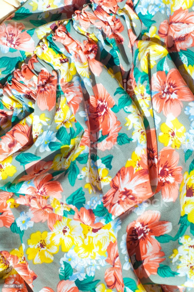 Texture, background, pattern. Girl's skirt. Silk fabric with floral pattern. Red Yellow Flowers stock photo