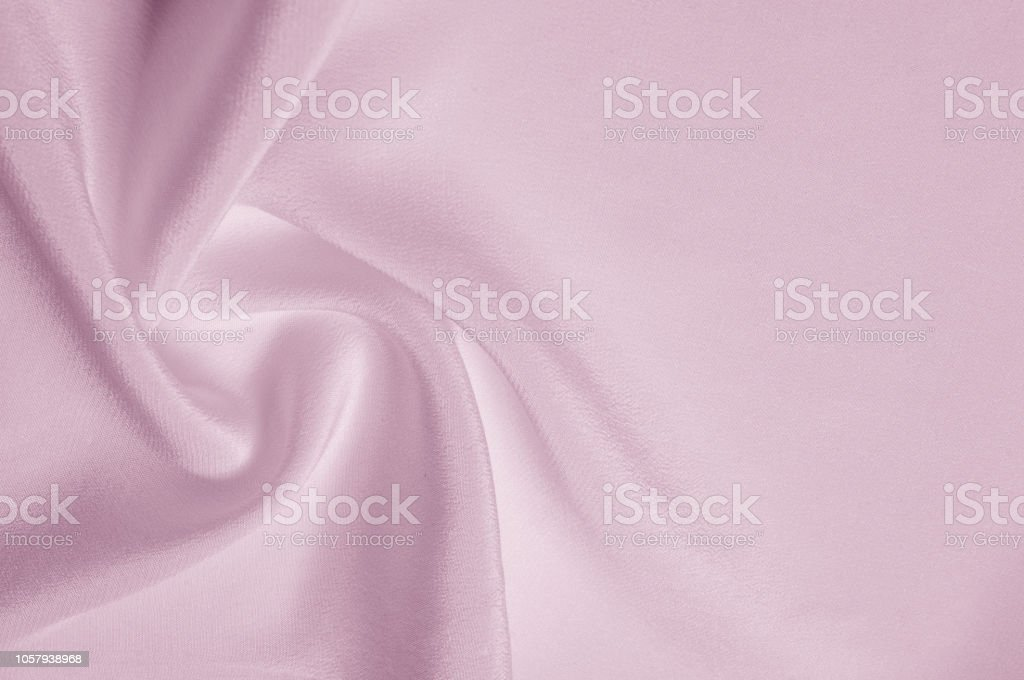 Texture background pattern. Pink silk fabric. Closeup of a rippled...
