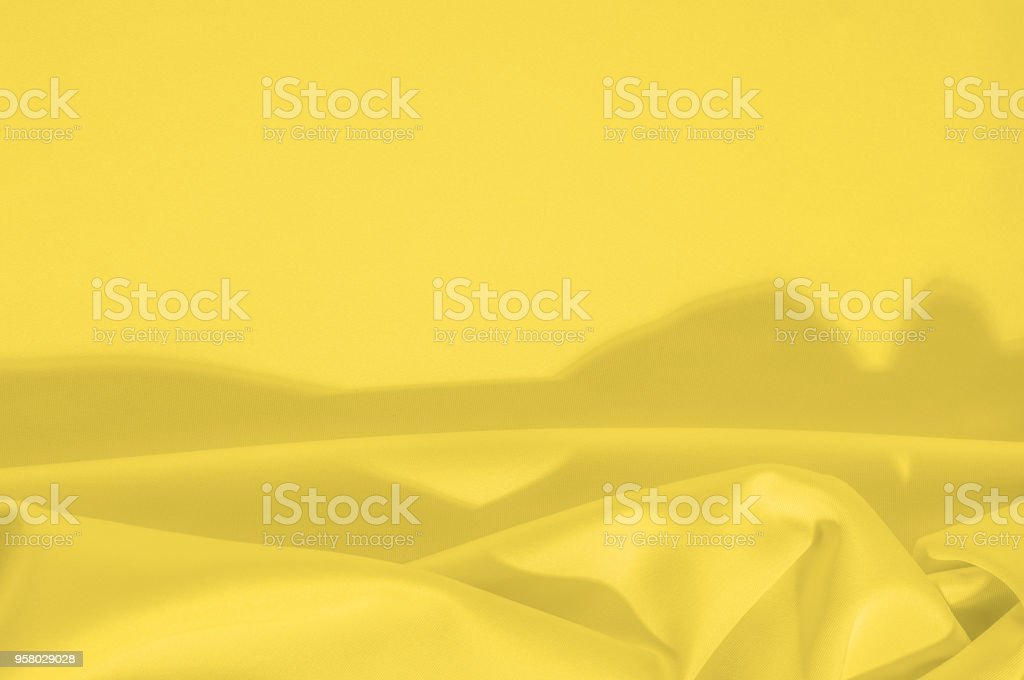 Texture Background. Template. Cloth - silk yellow. This yellow creme silk crepe de сhina shows a simple elegance. The creamy tone of ivory is textured with wrinkle waves, as it can boast a subtle sheen stock photo